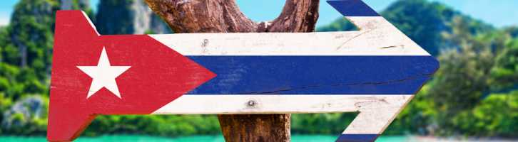 Cuba flag painted on an arrow signpost, on a beach.