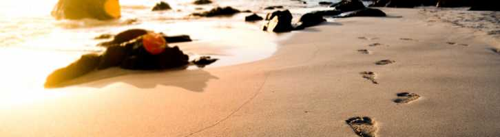 Footprints in the sand on the beach representing 10 steps to becoming an independent vacation rental owner