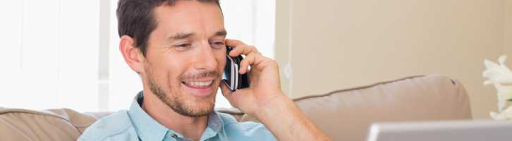 Man talking on phone smiling following up for repeat bookings