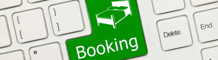 Green booking button on a keyboard to illustrate online vacation rental bookings