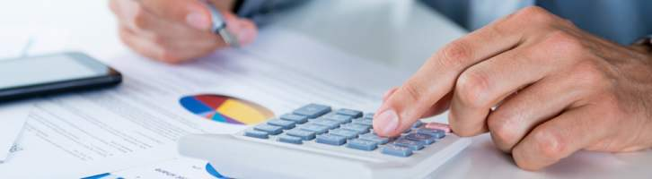 Person using a calculator while looking at reports and diagrams managing your rental property