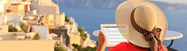 Woman on a tablet sitting on a balcony on holiday using the cloud to manager her property